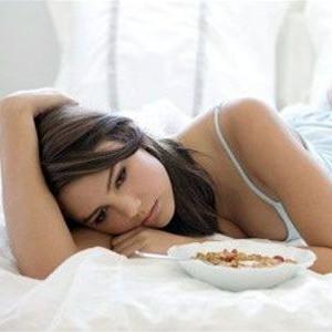 Женщина грустит лежа в кровати