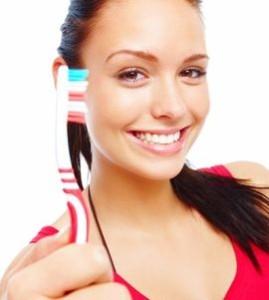 Девушка держит зубную щетку