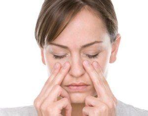 Женщина массирует нос