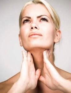Женщина пальпирует свое горло